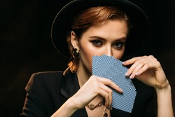 attractive girl in jacket and hat covering face with poker cards isolated on black, looking at camera