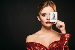 attractive girl in red shiny dress covering eye with joker card isolated on black