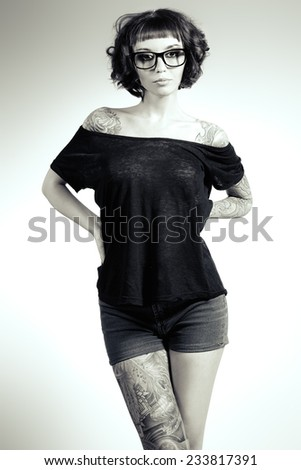 Stock Photo Attractive girl in spectacles alluring in sexual clothes. Beauty, fashion. Black-and-white photo.