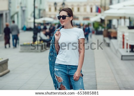 Attractive girl in sunglasses walking along the street. White t-shirt. Mock-up. #653885881