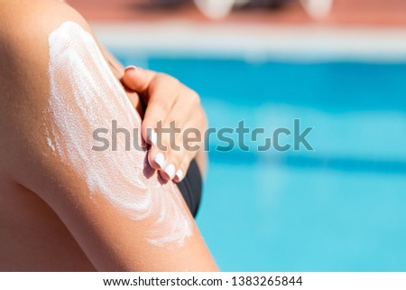 Attractive girl in sunhat applying sunscreen on shoulder by the pool. Sun Protection Factor in vacation, concept. #1383265844