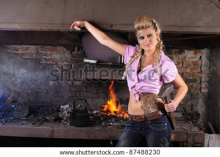 attractive girl in the smithy with hammer in her hand