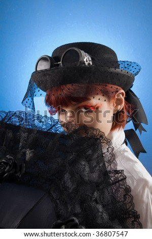 Attractive girl in Victorian style clothes with umbrella, studio shot over blue background
