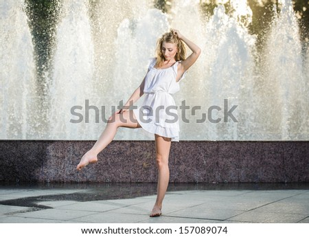 Attractive girl in white short dress sitting in front of a fountain in the summer hottest day. Girl with dress partly wet dancing. Beautiful blonde women near the fountain in a ballet position