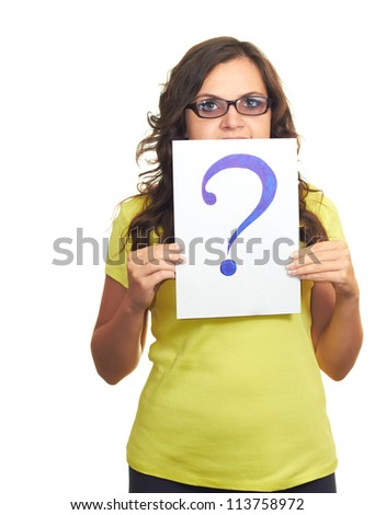 Attractive girl in yellow shirt and glasses holding a sheet of paper with a big question mark, covering her face. Isolated on white background