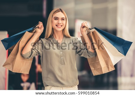 Attractive girl is holding shopping bags, looking at camera and smiling while standing in the mall #599010854