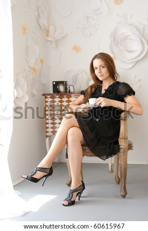 Attractive girl is sitting in a chair with a cup of coffee