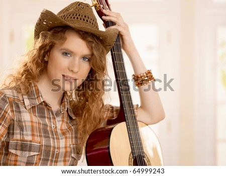 Attractive girl leaning on guitar, dressed in country style.?
