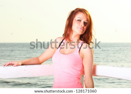 Attractive girl on pier winter in hair Young woman on background of sea sky