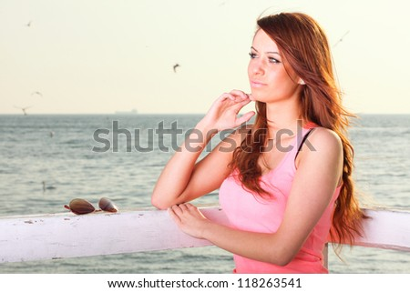 Attractive girl on pier Young woman on background of sea
