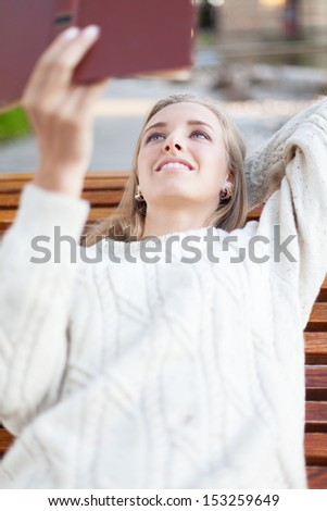 Attractive girl reading a book in the park - stock photo