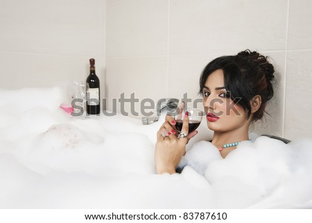 attractive girl relaxing in Jacuzzi and drinking red wine
