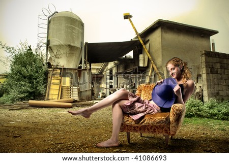 attractive girl seated on armchair with farm in the background