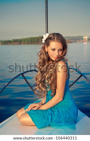 Attractive girl seating on a yacht on summer day