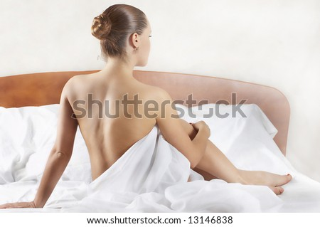 attractive girl sits on beds (type behind)