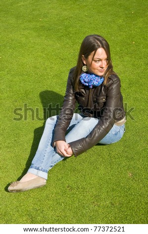 Attractive girl sitting on a green lawn. Spring.