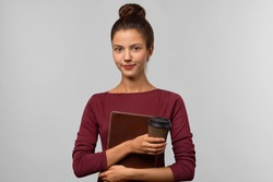 Attractive girl student holding a folder with educational supplies and a Cup of coffee. Tense and mixed emotions on her face. Studio portrait on isolated background. The concept of training.