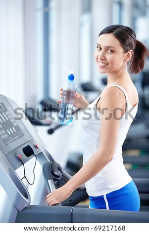 Attractive girl with a bottle of water on the treadmill