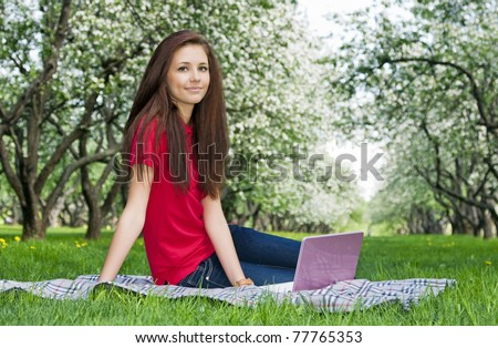 Attractive girl with a laptop in the park
