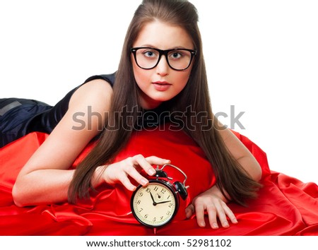 Attractive girl with alarm clock wearing glasses in the bed with red blanket