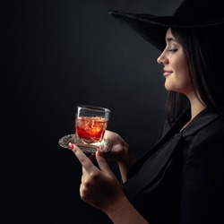 Attractive girl with alcoholic drink in frozen glass. Beautiful brunette in black hat holding glass with cold cocktail.