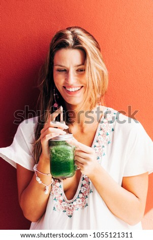 Attractive girl with blue eyes smiling and sipping on green juice in the shade