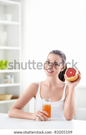 Attractive girl with grapefruit and a glass of juice