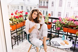 Attractive girl with long hair in pajama having breakfast on balcony in the morning in city. She holds a cup and smiling to camera