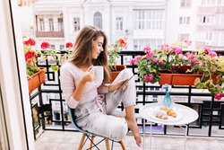 Attractive girl with long hair in pajama having breakfast on balcony in the morning in city. She holds a cup, reading on tablet