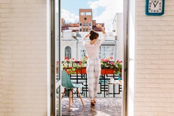 Attractive girl with long hair in pajama having breakfast on balcony in the morning in city. She holds a cup, she happy dances