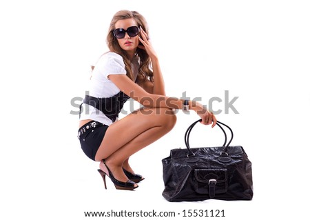 Attractive girl with sexy dress and big fashion bag sitting on the floor. Isolated on white