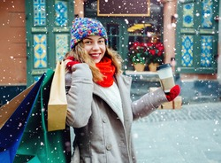 Attractive girl with shopping bags holding disposable cup with warm drink. Woman near the shop with gifts enjoying winter and dressed in warm bright  hat, red scarf and mittens. Magic snowfall effect.