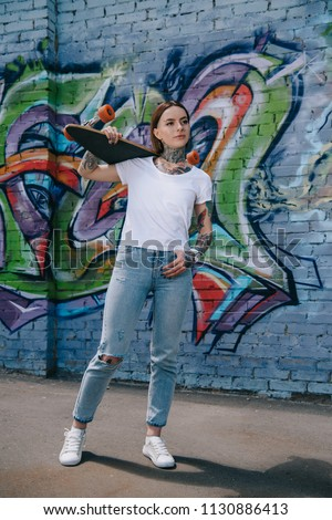 Stock Photo attractive girl with tattoos holding skateboard over shoulder near wall with graffiti