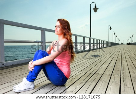 Attractive girl Young woman on pier Sits Relaxing Old Wooden Pier