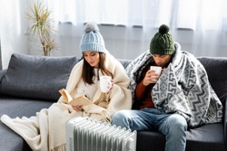 attractive girlfriend reading book and boyfriend in winter outfit with cup warming up near heater