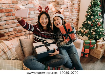 attractive girlfriends exchanging gifts at home on christmas eve. young girls taking selfie on the couch. cute christmas girls showing presents to the cellphone friends.