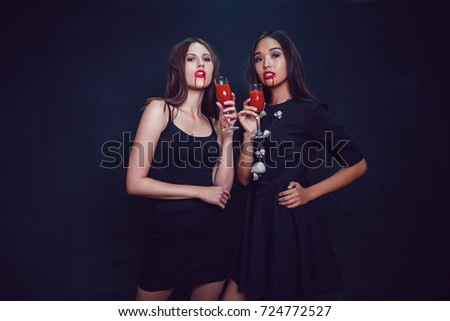 Stock Photo Attractive girls in the image of vampires hold glasses with blood. Halloween.