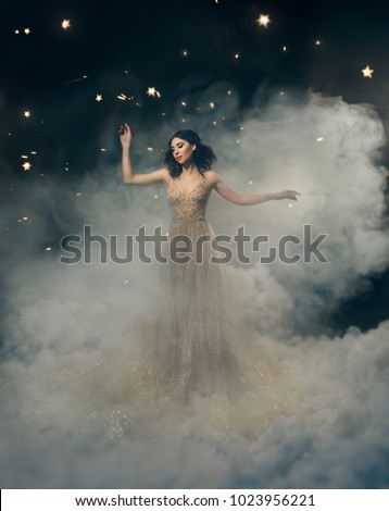 attractive goddess stands in the clouds in a luxurious, gold, sparkling dress. Whimsical hairstyle. Against the backdrop of a star and space. Art Photography. Cute princess in fog, mist, haze smoke