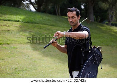 Attractive golf player checking the time while walk on beautiful golf course, male golf player at the course with a club sack, professional golfer carrying his bag while walking to the next hole