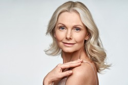 Attractive gorgeous mature older woman looking at camera isolated on white background advertising skincare spa treatment. Mid age tightening face skin care rejuvenation cosmetics concept. Portrait