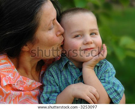 Attractive grandmother giving her young grandson a kiss on the cheek; selective focus on the boy