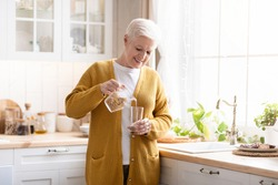 Attractive grandmother in casual outfit pouring spring water into glass in cozy kitchen, copy space. Smiling grey-haired senior woman drinking water while cooking, home interior