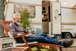 Attractive grey-haired man resting on the wooden deck chair using laptop with caravan van behind