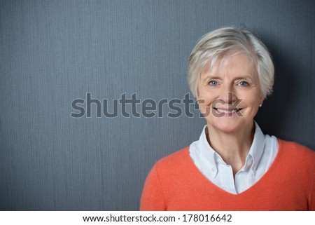 Attractive grey-haired senior woman with a beaming smile posing against a dark grey background with copyspace and vignetting