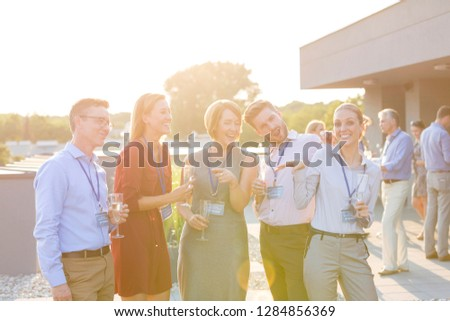 Attractive group of friends or office workers talking amongst themselves on a roof terrace at a restaurant or bar after a convention conference