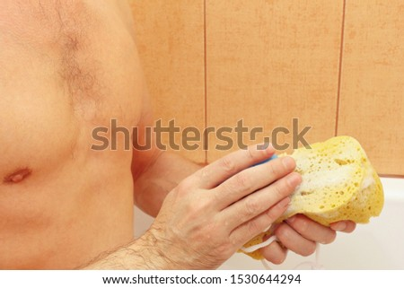 Attractive guy lathering a yellow sponge with soap