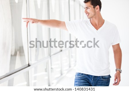 Attractive Guy pointing out the window as he is walking through a Penthouse