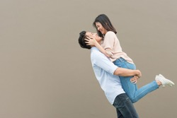 Attractive happy Asian couple in love having fun and hugging. Man lifting woman
