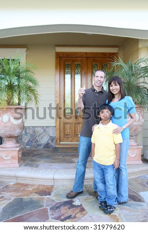 Attractive happy family outside their home with key