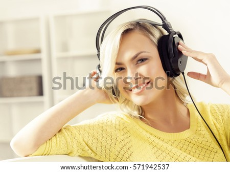 Attractive happy girl listening music at home. #571942537